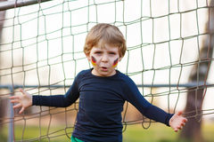 Blond boy of 4 playing soccer with football on football field Royalty Free Stock Image