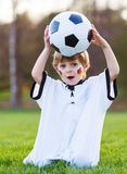 Blond boy of 4 playing soccer with football on football field Stock Images