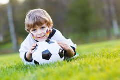 Blond boy of 4 playing soccer with football on football field Royalty Free Stock Photography