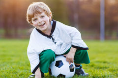 Blond boy of 4 playing soccer with football on football field Stock Photos