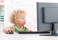 A blond boy plays with a computer Stock Photo