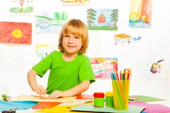 Blond boy on preschool art class. One happy boy on creative craft preschool class with pencils, images and cardboard in the room stock photos
