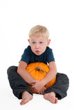 Blond boy with a pumpkin Royalty Free Stock Photos