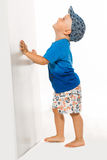 Blond boy pushing he wall white bacground,. Space for text Royalty Free Stock Photography