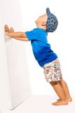 Blond boy pushing he wall white bacground. Space for text Royalty Free Stock Photography