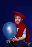 Blond boy in red scarf smiling with blue balloon. Blond boy in red scarf and beret smiling on blue background with blue balloon Royalty Free Stock Photo