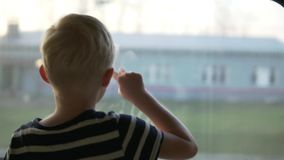 A blond boy is riding in a train. He looks at the village he is driving through. The child is standing at the window, the town's houses rush past stock footage
