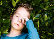 Blond boy rubbing his eyes stock image