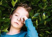 Blond boy rubbing his eyes Stock Image