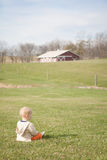 Blond Boy Sitting on a Field on a Farm Royalty Free Stock Photography