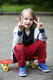 Blond boy sitting on skateboard and making the peace sign Royalty Free Stock Images