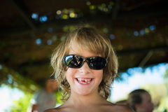 Blond boy smiling. The boy wears sunglasses Royalty Free Stock Photo