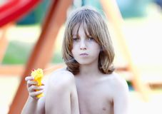 Blond Boy with Squirt Gun. Boy with Long Blond Hair Playing with Squirt Gun royalty free stock image