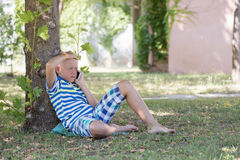 A blond boy talking on the smartphone Stock Photography