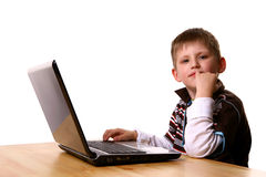 Blond boy thinking with notebook. Little blond boy thinking while using a notebook, cute kid in dark shirt, sitting behind the wooden table Royalty Free Stock Photo