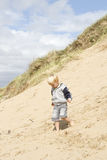 Blond boy walking down sand dune Royalty Free Stock Photos