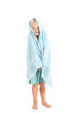 Blond boy wearing swimming shorts with a blue towel. Studio shot, isolated on a white background Royalty Free Stock Photography
