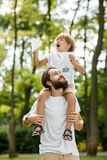 Blond boy wearing a white t-shirt sitting on the shoulders of his handsome bearded father and keeps a paper airplane in royalty free stock images