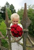 Happy bride breathes the scent of red roses behind the old castle fence stock photography