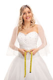 Blond bride measuring her waist Royalty Free Stock Image