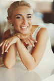 Blond bride smiles sincerely holding her chin in arms Royalty Free Stock Images