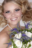 Blond bride with thick lashes. Smiling Attractive caucasian blond woman with thick lashes holding white roses Stock Images