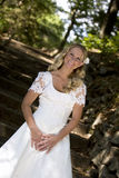 Blond bride in white dress. Happy young bride in traditional white wedding dress, countryside road and trees in background Royalty Free Stock Images
