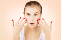 Blond brown eyed  girl  examines her skin with astonishment,pink Stock Images