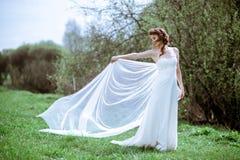 Blond brud i den vita bröllopsklänningen för mode med makeup Arkivbilder