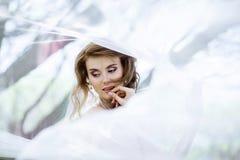 Blond brud i den vita bröllopsklänningen för mode med makeup Arkivfoto