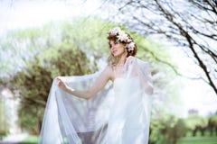 Blond brud i den vita bröllopsklänningen för mode med makeup Royaltyfria Bilder