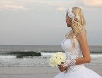 Blond brud som går på stranden. härlig kvinna i bröllopsklänningen som ser på havet. Fotografering för Bildbyråer