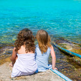 Blond and brunette kid girls sitting on beach port Stock Images