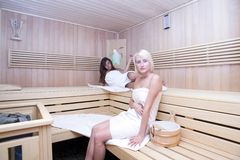 Blond and brunette in sauna stock image