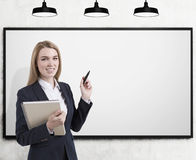 Blond business coach with marker, blank whiteboard. Portrait of a blond businesswoman holding a black marker and standing near an empty whiteboard ready to Royalty Free Stock Images