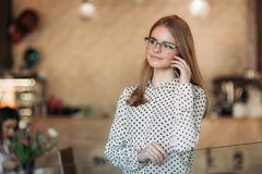 Blond Business lady with glasess use phone in cafe royalty free stock photos