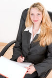 A blond business woman (4). A blond business woman sitting in a black chair writing in a folder Stock Image