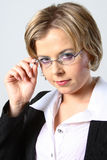 Blond business woman adjusting glasses. Blond business woman looking up at the camera adjusting her glasses royalty free stock image