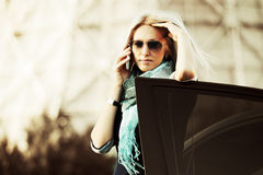 Fashion business woman calling on cell phone by her car Royalty Free Stock Images