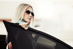 Blond business woman at the car Royalty Free Stock Photos