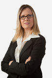 Blond business woman with eyeglasses. Portrait of blond woman in business suit with arms crossed wearing eyeglasses royalty free stock photo