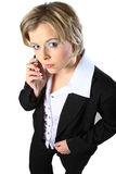 Blond business woman with glasses and phone. Blond business woman looking up at the camera using a cell phone royalty free stock photos