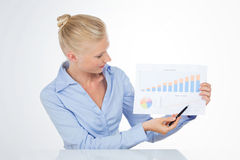 Blond business woman pointing a chart with pen Royalty Free Stock Photography