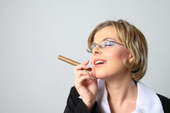 Blond business woman smoking a cigar Stock Photography