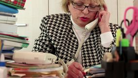 Blond business woman  talking on phone, writing down information stock footage