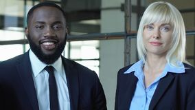 Blond businesslady and black man smiling on camera, race gender equality at work. Stock footage stock video footage