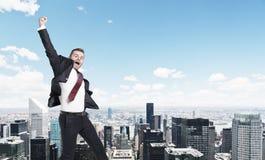 Blond businessman jumping, cityscape Stock Photo