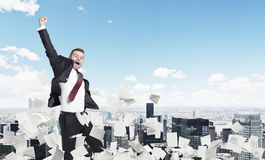 Blond businessman jumping, cityscape, papers Royalty Free Stock Images