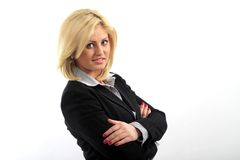 Blond businesswoman. Side portrait of blond businesswoman with arms folded; white studio background Stock Photo