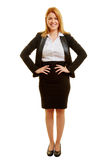 Blond businesswoman with arms akimbo. Blond smiling businesswoman with arms akimbo Stock Photography